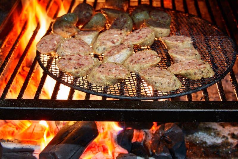 Salsiccie grigliate in fiamma alla griglia fotografia stock