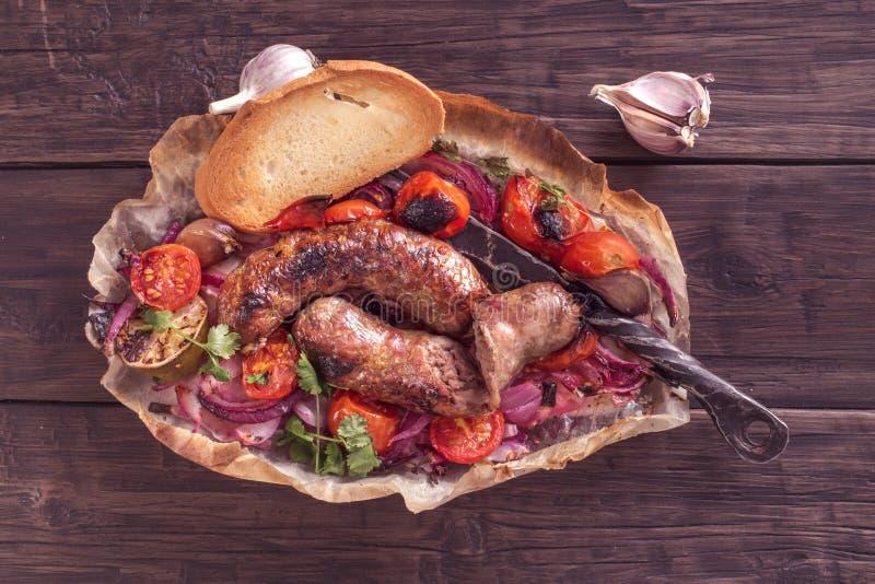 Salsiccie rustiche con la cipolla ed i pomodori sulla tavola fotografie stock libere da diritti