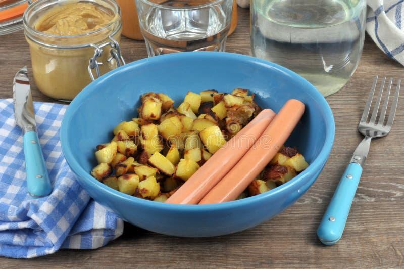 Salsiccie viennesi con le patate fritte su un piatto fotografia stock