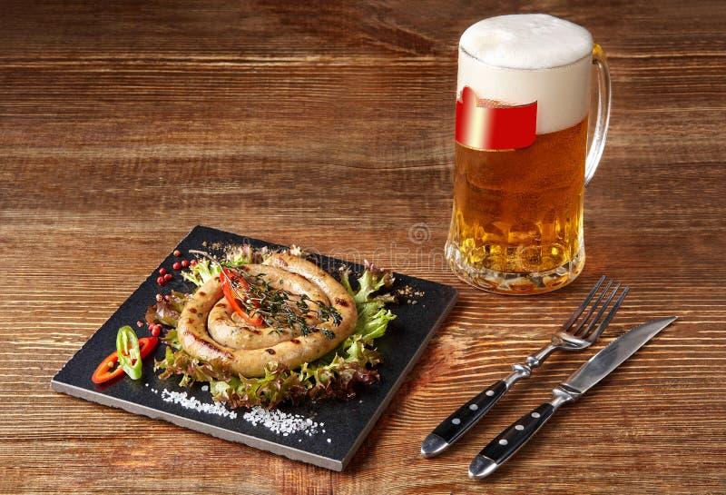 Salsicha caseiro com alho e especiarias em uma placa da ardósia, um vidro da cerveja atrás da placa na tabela de madeira fotos de stock royalty free