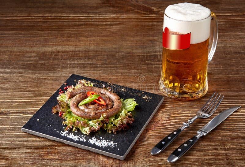 Salsicha caseiro com alho e especiarias em uma placa da ardósia, um vidro da cerveja atrás da placa na tabela de madeira imagens de stock royalty free