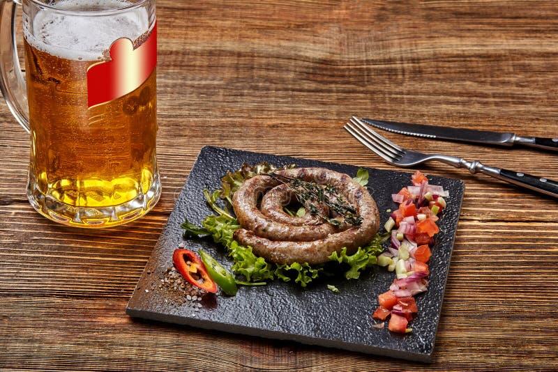 Salsicha caseiro com alho e especiarias em uma placa da ardósia, um vidro da cerveja atrás da placa na tabela de madeira fotos de stock