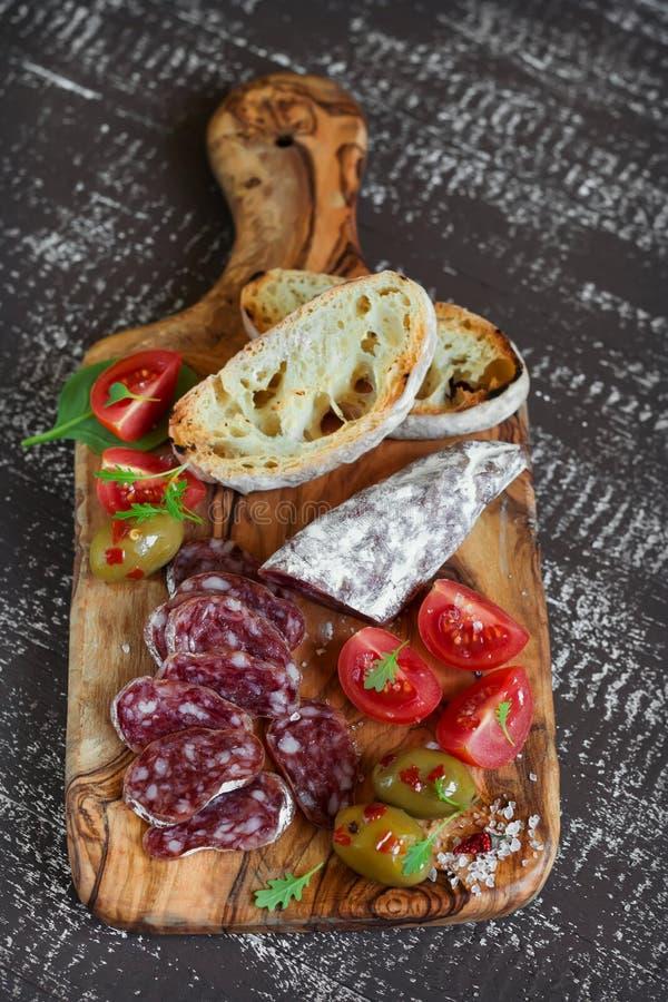 Salsicha, ciabatta, azeitonas e tomates de cereja italianos na placa verde-oliva fotos de stock royalty free