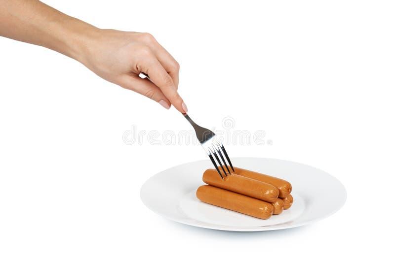 Salsicha da carne para o cachorro quente ou assado na placa à disposição Isolado no fundo branco Refeição do fast food imagem de stock