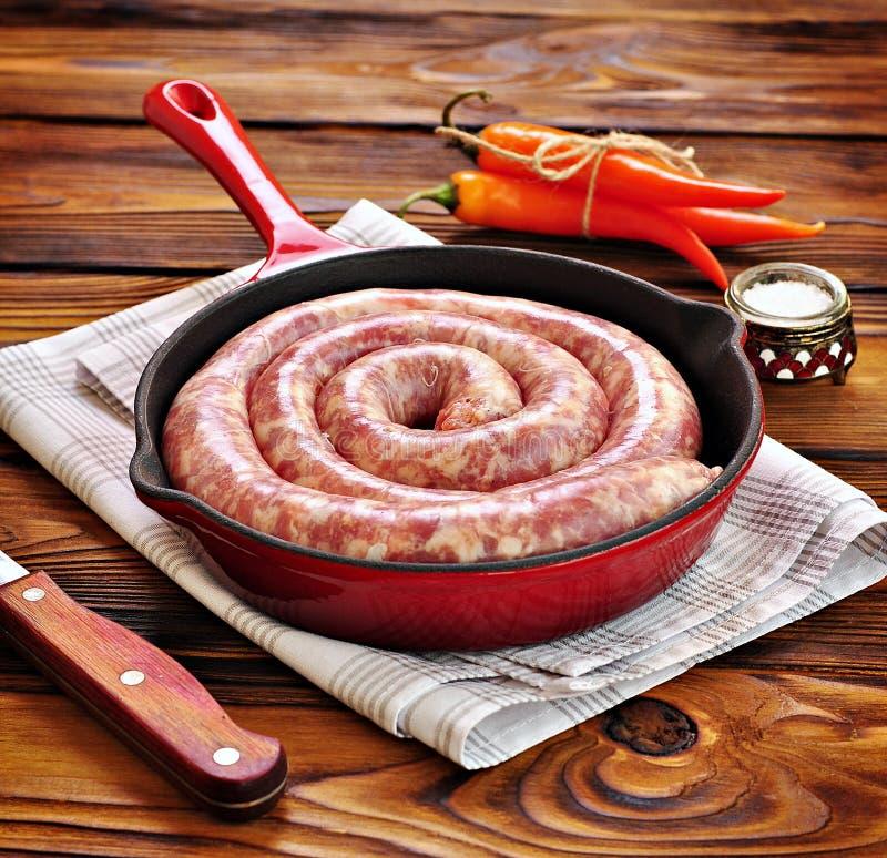 Salsicha de carne de porco crua em uma frigideira do ferro fundido em um fundo de madeira imagens de stock royalty free