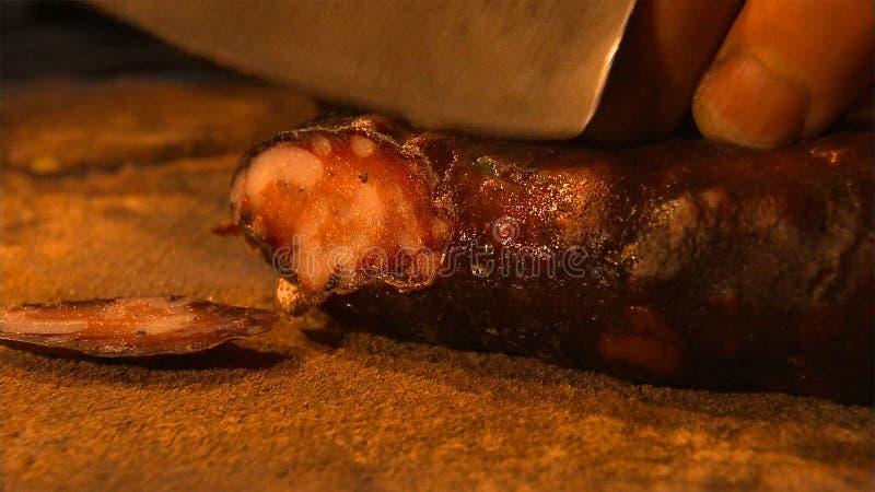 Salsicha de sangue caseiro na porcelana do campo, cortando com uma faca imagem de stock