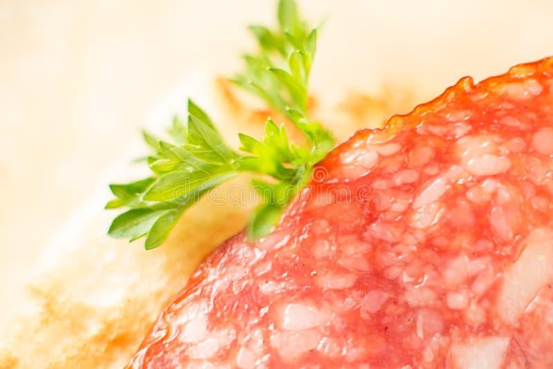 Salsicha do salame em uma fatia de tiro macro do pão branco fotografia de stock
