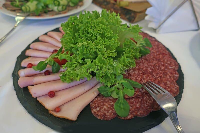 Salsicha e presunto cortados com as folhas da salada verde em uma placa preta foto de stock royalty free