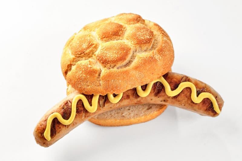 Salsicha em um rolo de pão duro com mostarda amarela imagem de stock