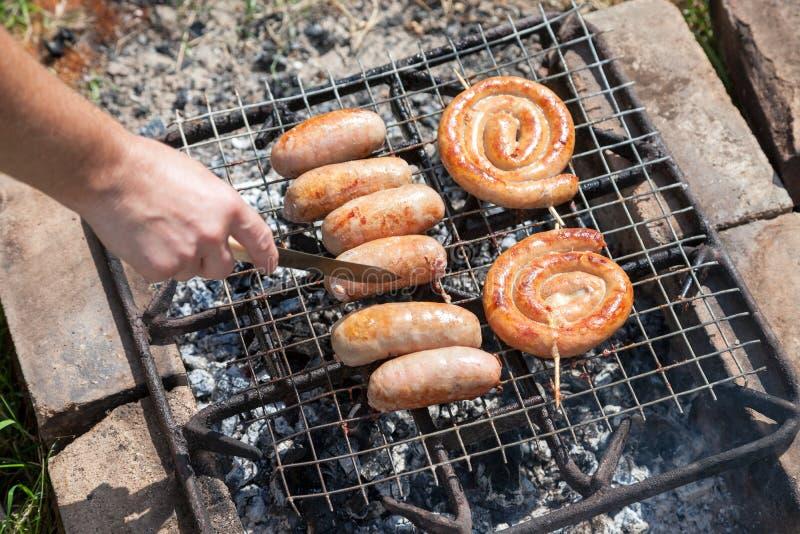 Salsicha fresca e cachorros quentes que grelham fora fotografia de stock royalty free