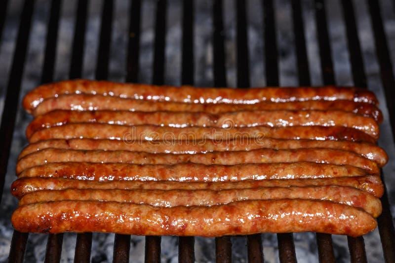 Salsicha fresca e cachorros quentes que grelham fora em um assado g do gás fotografia de stock