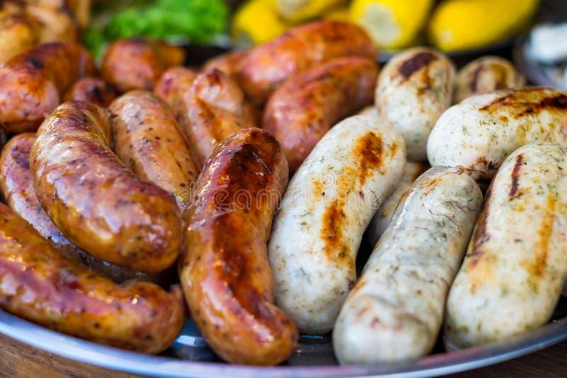 Salsicha fresca e cachorros quentes que grelham fora em uma grade do assado do gás fotos de stock