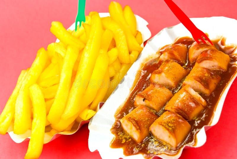 Salsicha fritada, caril, com fritadas francesas imagens de stock