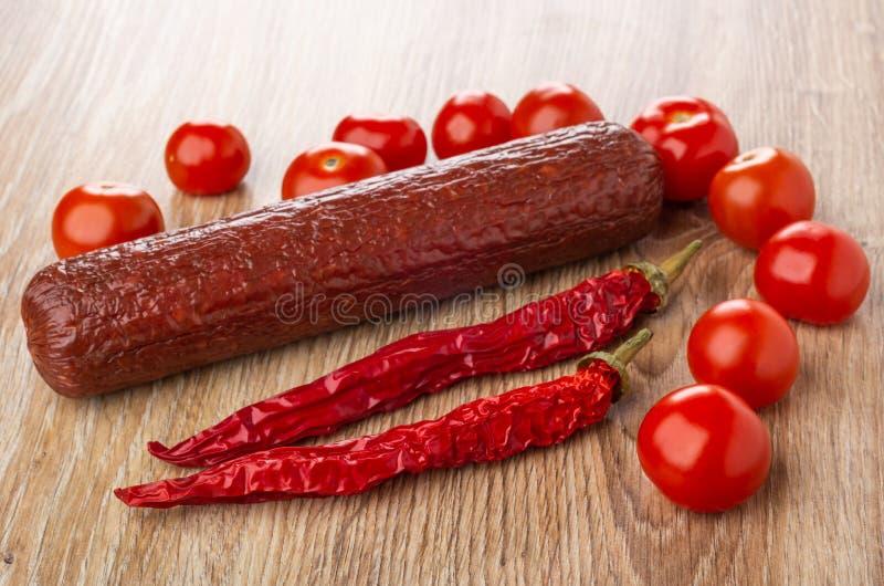 Salsicha fumada, tomate, pimenta de pimentão na tabela de madeira foto de stock royalty free