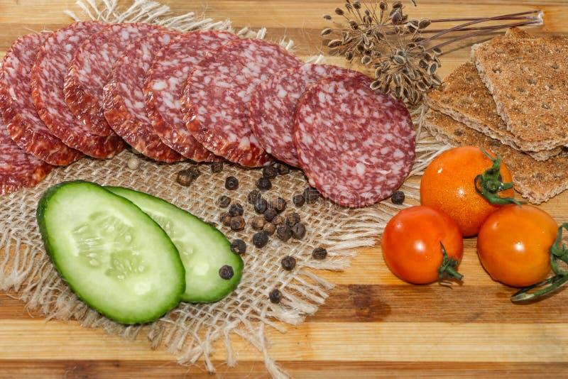Salsicha fumado cortada com bacon e pepino verde cortado e três tomates vermelhos cereja e partes de pães ralados do centeio imagem de stock