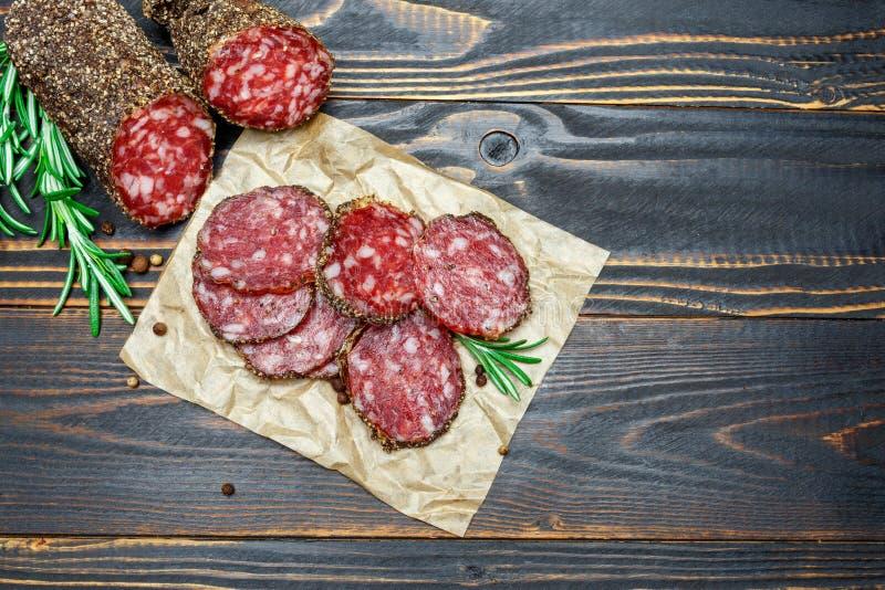 Salsicha orgânica secada do salame coberta com a pimenta no fundo de madeira imagens de stock royalty free