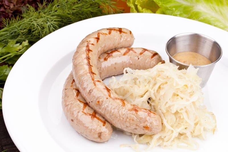 Salsichas alemãs com o chucrute na placa branca fotografia de stock