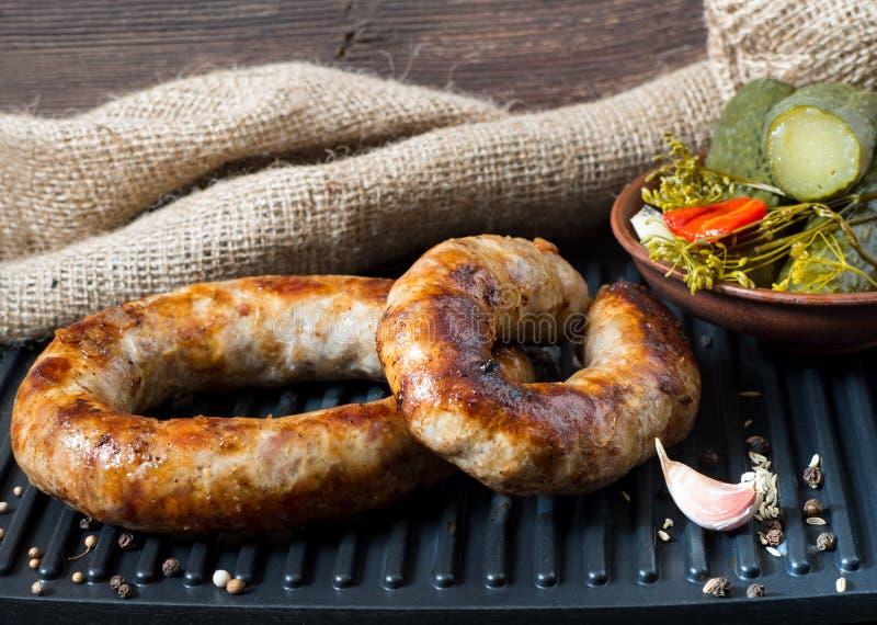 Salsichas caseiros picantes carne de porco e salsichas da carne grelhadas com molho, especiarias e o pepino conservado Molde no e fotografia de stock