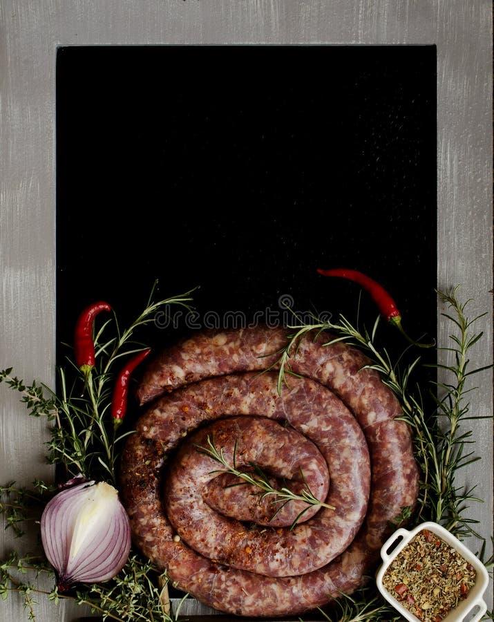 Salsichas cruas da carne em uma bandeja do ferro fundido, foco seletivo fotografia de stock