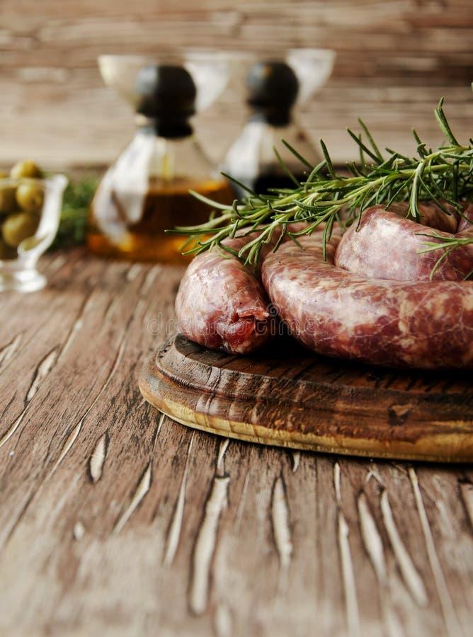 Salsichas cruas da carne em uma bandeja do ferro fundido, foco seletivo imagens de stock