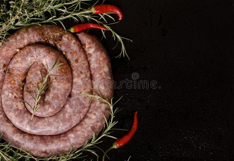 Salsichas cruas da carne em uma bandeja do ferro fundido, foco seletivo foto de stock royalty free