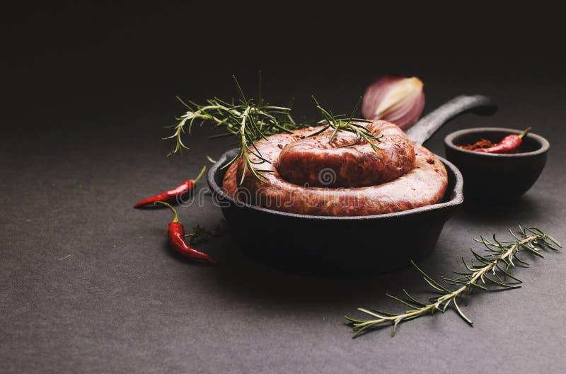 Salsichas cruas da carne em uma bandeja do ferro fundido, foco seletivo fotos de stock royalty free