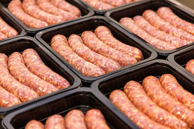 Salsichas da carne crua na caixa de embalagem imagens de stock royalty free