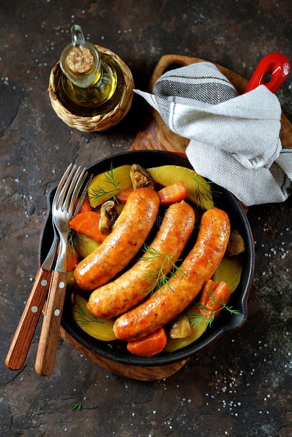Salsichas do frango assado com batatas, cebolas, cenouras e cogumelos em uma bandeja do ferro fundido Vista superior fotos de stock royalty free