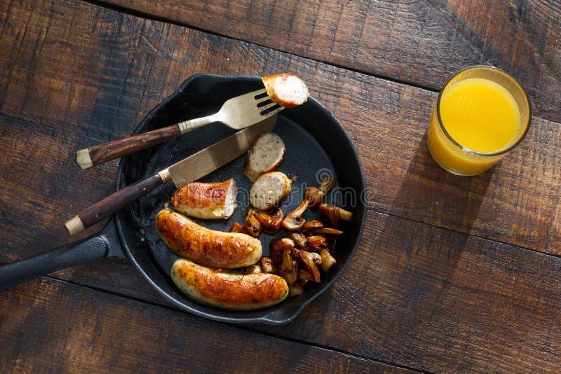 Salsichas do frango frito da vista superior, cogumelos na bandeja com ju alaranjado imagem de stock royalty free