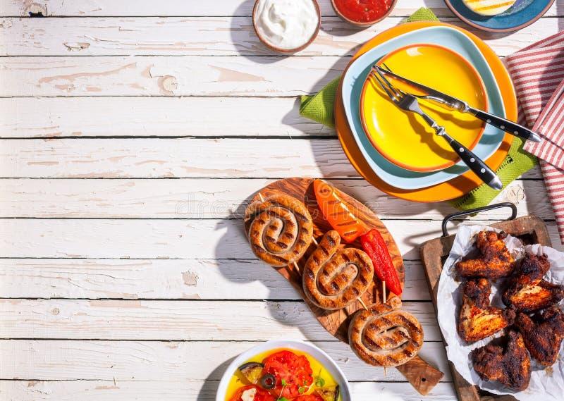 Salsichas e asas de galinha grelhadas na tabela de piquenique foto de stock royalty free