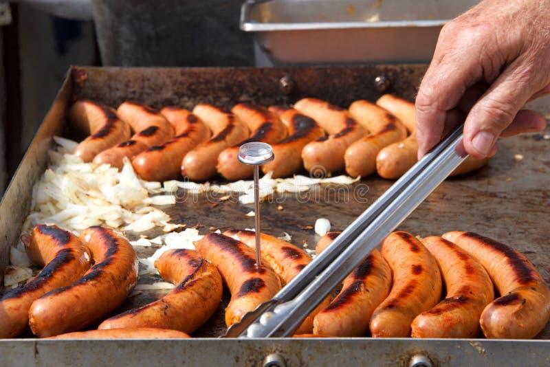 Salsichas e cebolas do cachorro quente que grelham com giro da mão imagem de stock