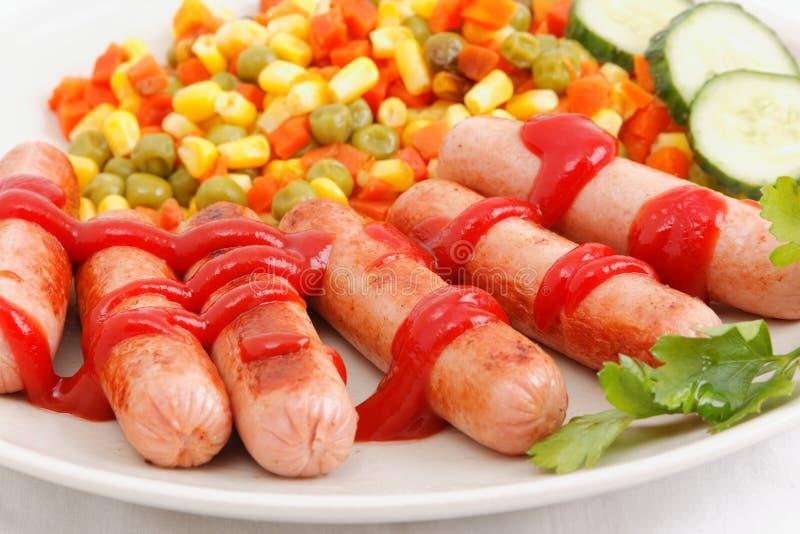 Salsichas e vegetais grelhados em uma placa imagem de stock royalty free