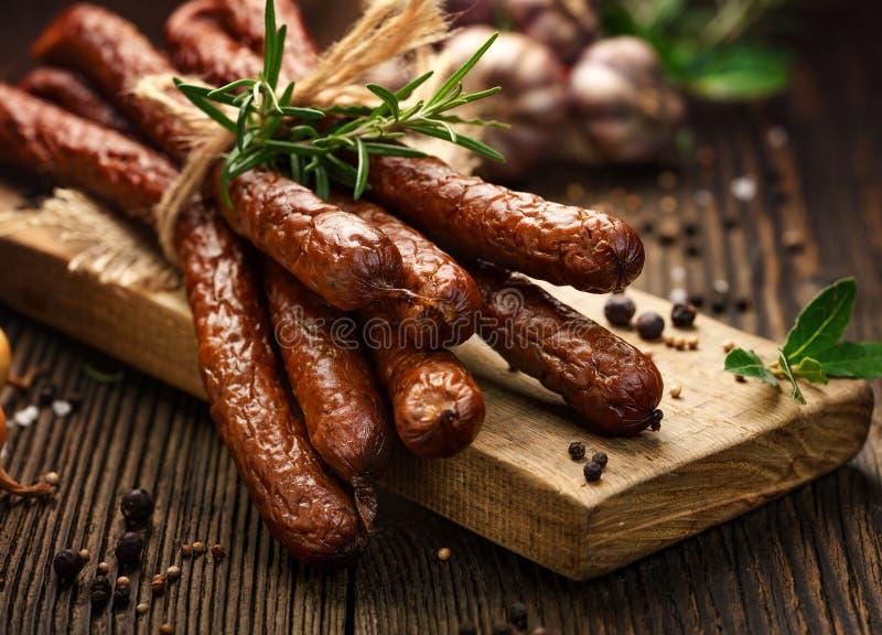 Salsichas em uma tabela rústica de madeira com adição das ervas e das especiarias aromáticas frescas, produto natural da exploraç fotos de stock
