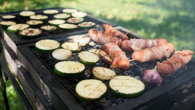 Salsichas envolvidas no bacon e nos vegetais na grade imagem de stock royalty free