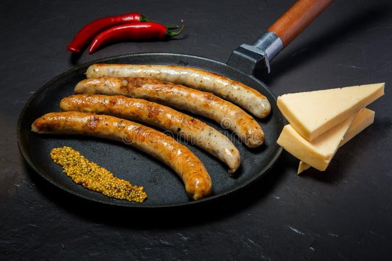 Salsichas finas fritadas feitos a m?o, mostarda, piment?o, e queijo duro imagem de stock royalty free