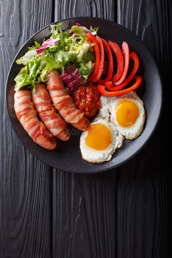 Salsichas fritadas caseiros envolvidas no bacon, nos ovos, no molho e em fresco fotografia de stock