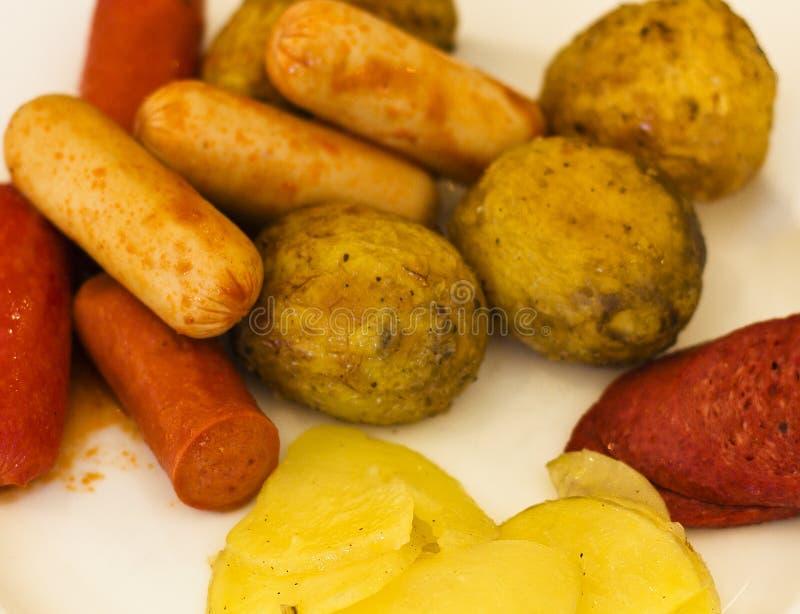 Salsichas fritadas com batatas cozidas em uma placa branca F seletivo imagens de stock royalty free