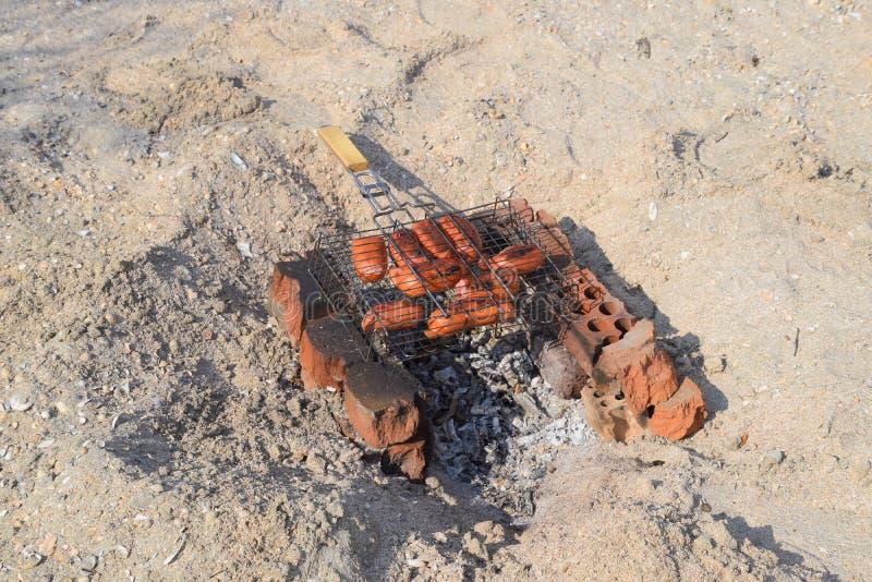 Salsichas fritadas em um fogo imagens de stock