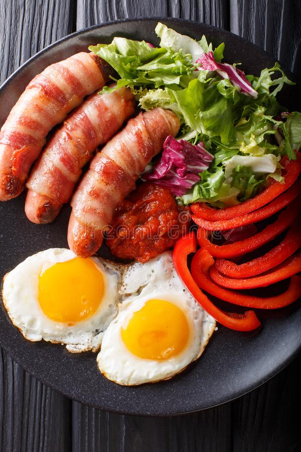 Salsichas fritadas envolvidas no bacon, nos ovos e no close-up fresco da salada foto de stock royalty free