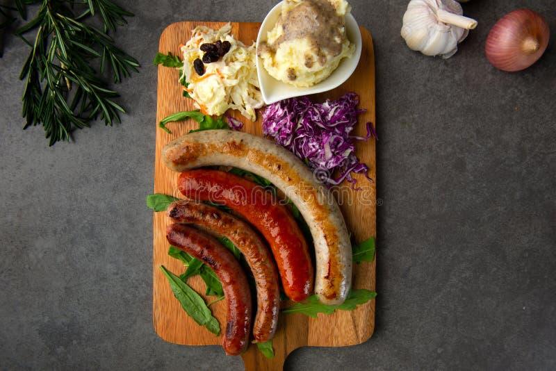 Salsichas grelhadas com as batatas de erva-benta na placa de madeira foto de stock