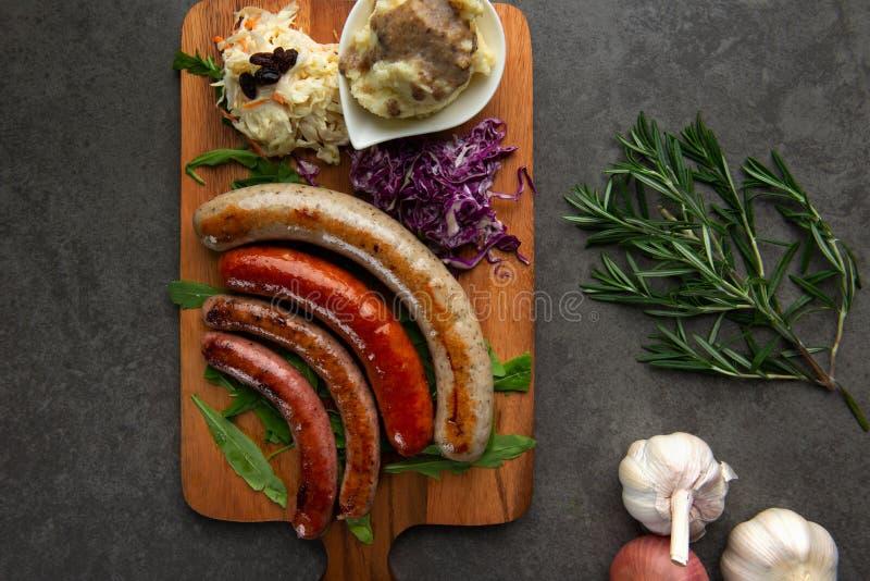 Salsichas grelhadas com as batatas de erva-benta na placa de madeira fotos de stock