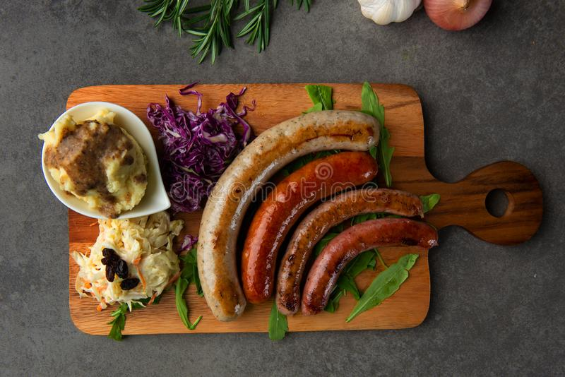 Salsichas grelhadas com as batatas de erva-benta na placa de madeira fotografia de stock royalty free