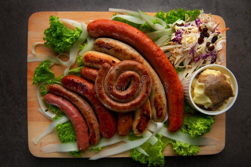 Salsichas grelhadas com as batatas de erva-benta na placa de madeira fotos de stock royalty free