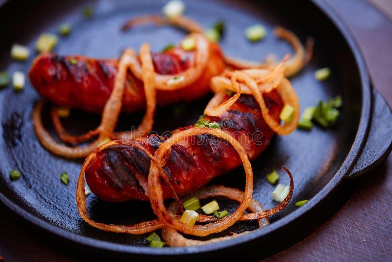 Salsichas grelhadas com as cebolas na placa Conceito do alimento fotografia de stock