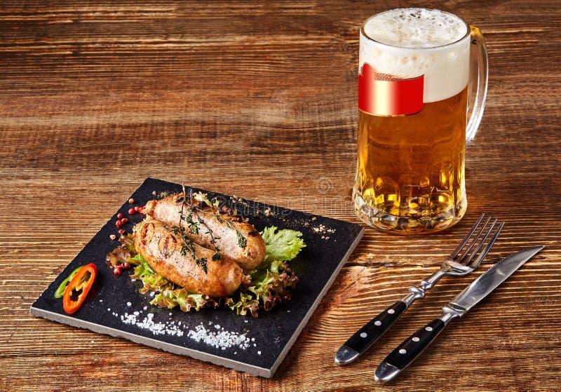 Salsichas grelhadas com cerveja na tabela de madeira Vista superior imagem de stock royalty free