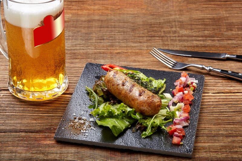 Salsichas grelhadas com cerveja na tabela de madeira Vista superior fotografia de stock royalty free