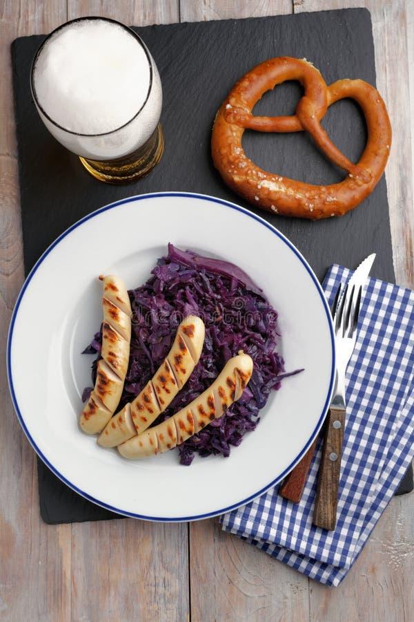 Salsichas grelhadas com couve, cerveja, e o pretzel assados imagens de stock
