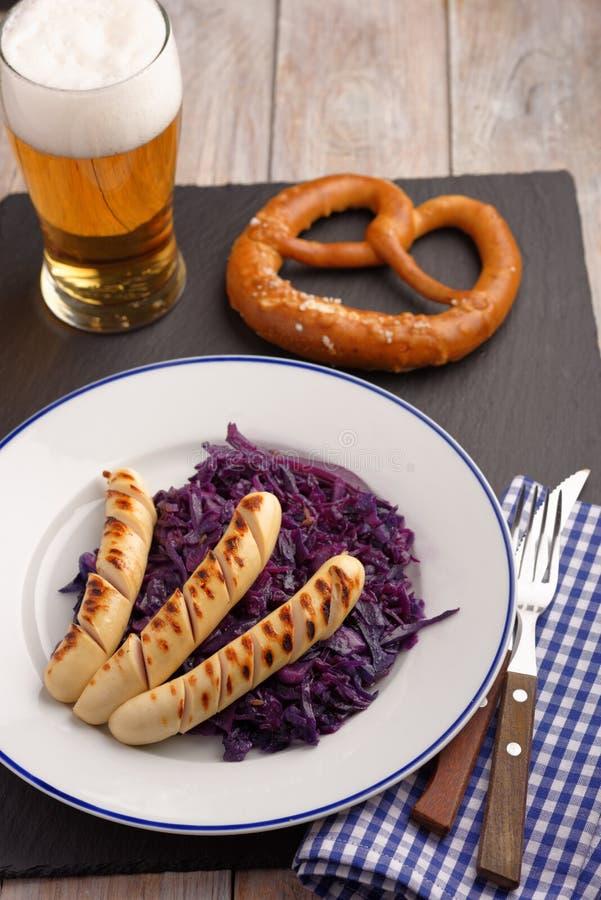 Salsichas grelhadas com couve, cerveja, e o pretzel assados foto de stock