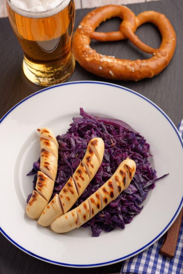 Salsichas grelhadas com couve, cerveja, e o pretzel assados fotografia de stock