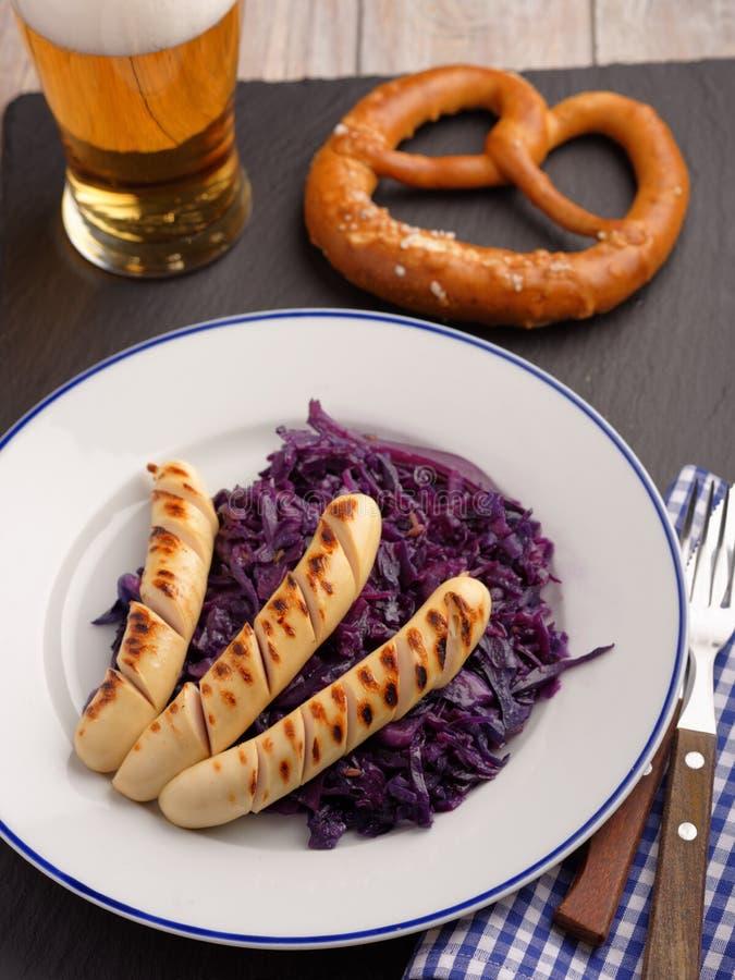 Salsichas grelhadas com couve, cerveja, e o pretzel assados imagem de stock